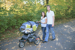 Smiling couple with baby stroller in a park Stock Image