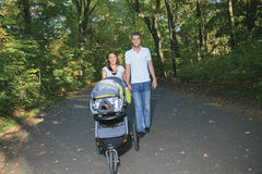 Smiling couple with baby stroller in a park Royalty Free Stock Photos