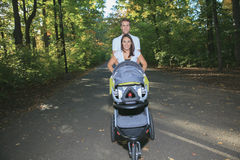 Smiling couple with baby stroller in a park Stock Photos