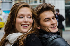 Smiling Couple Back To Back. Closeup of smiling couple back to back outdoors Royalty Free Stock Image