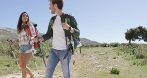 Smiling couple backpacking. Young happy couple with backpacks and trekking poles walking down road in mountains under sun light stock footage