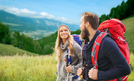 Smiling couple with backpacks hiking. Adventure, travel, tourism, hike and people concept - smiling couple walking with backpacks over alpine hills background Stock Images