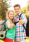 Smiling couple with backpacks showing thumbs up Royalty Free Stock Images