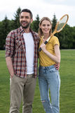 Smiling couple with badminton racquet standing together in park Stock Photos