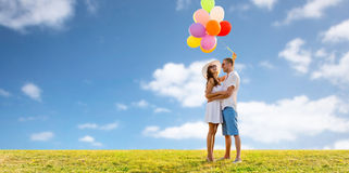Smiling couple with balloons over sky and grass. Love, holidays, summer, dating and people concept - smiling couple wearing sunglasses with balloons hugging over Royalty Free Stock Image