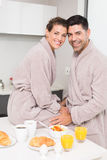 Smiling couple in bathrobes having breakfast together Royalty Free Stock Image