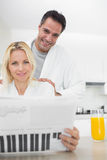 Smiling couple in bathrobes reading newspaper in kitchen Royalty Free Stock Photos
