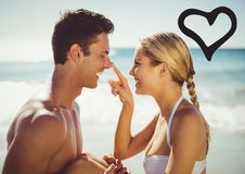 Smiling couple on beach with black heart Stock Image