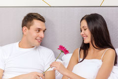 Smiling couple in bed with flower. Hotel, travel, relationships, holidays and happiness concept - smiling couple in bed with pink flower Stock Image
