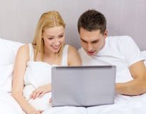 Smiling couple in bed with laptop computer Royalty Free Stock Images