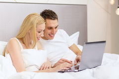 Smiling couple in bed with laptop computer Stock Images