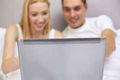 Smiling couple in bed with laptop computer Stock Image
