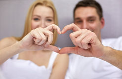 Smiling couple in bed making heart shape gesture Stock Image