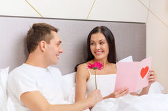 Smiling couple in bed with postcard and flower. Hotel, travel, relationships, holidays and happiness concept - smiling couple in bed with postcard and pink Stock Images