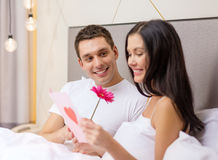 Smiling couple in bed with postcard and flower. Hotel, travel, relationships, holidays and happiness concept - smiling couple in bed with postcard and pink Royalty Free Stock Images