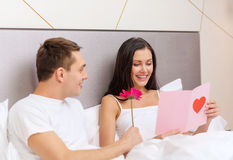 Smiling couple in bed with postcard and flower. Hotel, travel, relationships, holidays and happiness concept - smiling couple in bed with postcard and pink Royalty Free Stock Photos