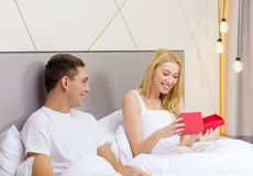 Smiling couple in bed with red gift box Stock Images