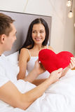 Smiling couple in bed with red heart shape pillow Stock Photos