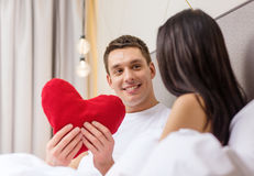 Smiling couple in bed with red heart shape pillow Stock Photography