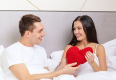 Smiling couple in bed with red heart shape pillow Stock Images