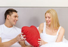 Smiling couple in bed with red heart shape pillow Stock Image