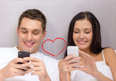 Smiling couple in bed with smartphones Stock Images