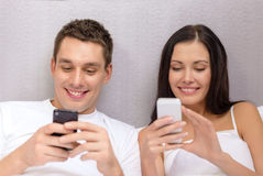 Smiling couple in bed with smartphones Stock Photos