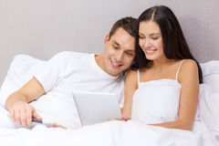 Smiling couple in bed with tablet pc computers Stock Image