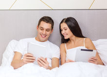 Smiling couple in bed with tablet pc computers Royalty Free Stock Photo