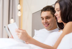 Smiling couple in bed with tablet pc computers Royalty Free Stock Photos