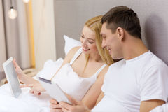 Smiling couple in bed with tablet pc computers Stock Photo
