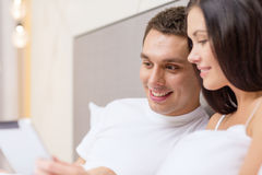 Smiling couple in bed with tablet pc computers Royalty Free Stock Image