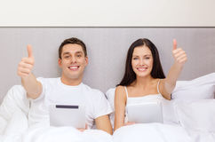 Smiling couple in bed with tablet pc computers Royalty Free Stock Photography
