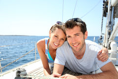 Smiling couple being happy cruising on sailing boat stock photography