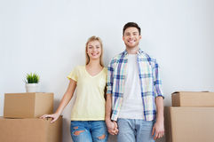 Smiling couple with big boxes moving to new home Stock Images