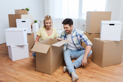 Smiling couple with big boxes moving to new home Royalty Free Stock Images