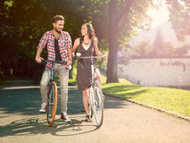 Smiling couple on the bike. In an alley with green trees on a sunny summer day Stock Photo