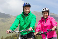 Smiling couple on a bike ride wearing hooded jumpers Royalty Free Stock Photos