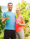 Smiling couple with bottles of water outdoors. Fitness, sport, friendship and lifestyle concept - smiling couple with bottles of water outdoors royalty free stock image