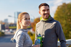 Smiling couple with bottles of water outdoors Royalty Free Stock Photos