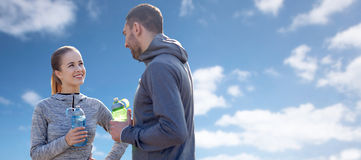 Smiling couple with bottles of water over blue sky Stock Images