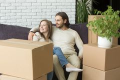Smiling couple with boxes sitting on sofa embracing, moving day. Smiling couple sitting on sofa embracing on moving in out day, married men and women planning stock photography
