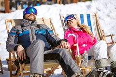 Smiling couple on break from skiing enjoy on sun. In ski loungers stock photos