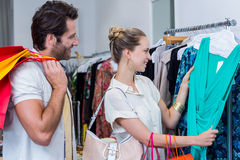 Smiling couple browsing clothes Stock Photos