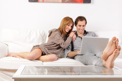 Smiling couple browsing the web at home Stock Photo
