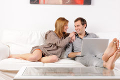 Smiling couple browsing the web at home Royalty Free Stock Image