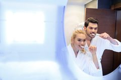 Smiling couple brushing teeth and looking at mirror. In bathroom stock photos