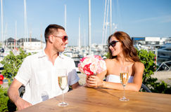 Smiling couple with bunch and champagne at cafe Stock Image