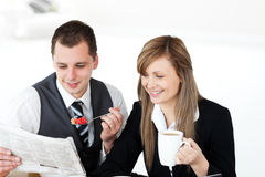 Smiling couple of businesspeople reading newspaper Royalty Free Stock Photos