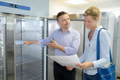 Smiling couple buying domestic refrigerator in supermarket royalty free stock images